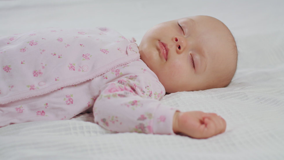 A baby sleeping sound on a white bed at