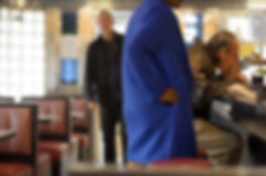 man eating at counter in diner with woman in blue coat waiting for takeout order