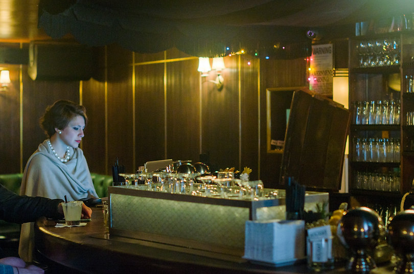 woman at bar with pearl necklace glasses in front of window with blinds