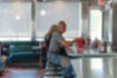 phone call in kitchen of restaurant behind red curtain