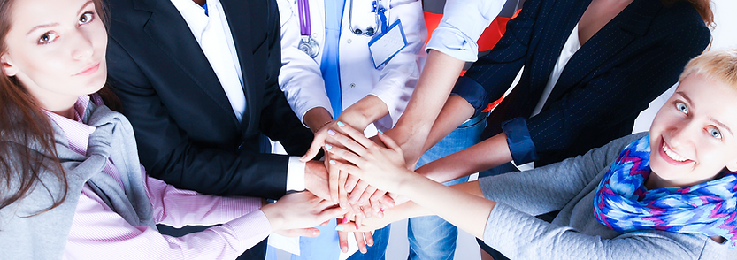 Doctors, patients, and agents in a circle placing their hands in the center of the group