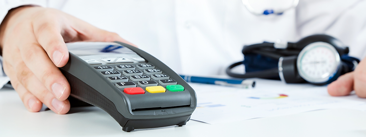Close up of a doctor pushing a credit card payment pad across a desk