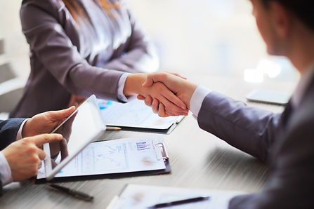 A man and a woman in business suits shaking hands over paperwork