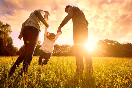 Husband, wife, and young daughter playing in a field with the sunset in the background