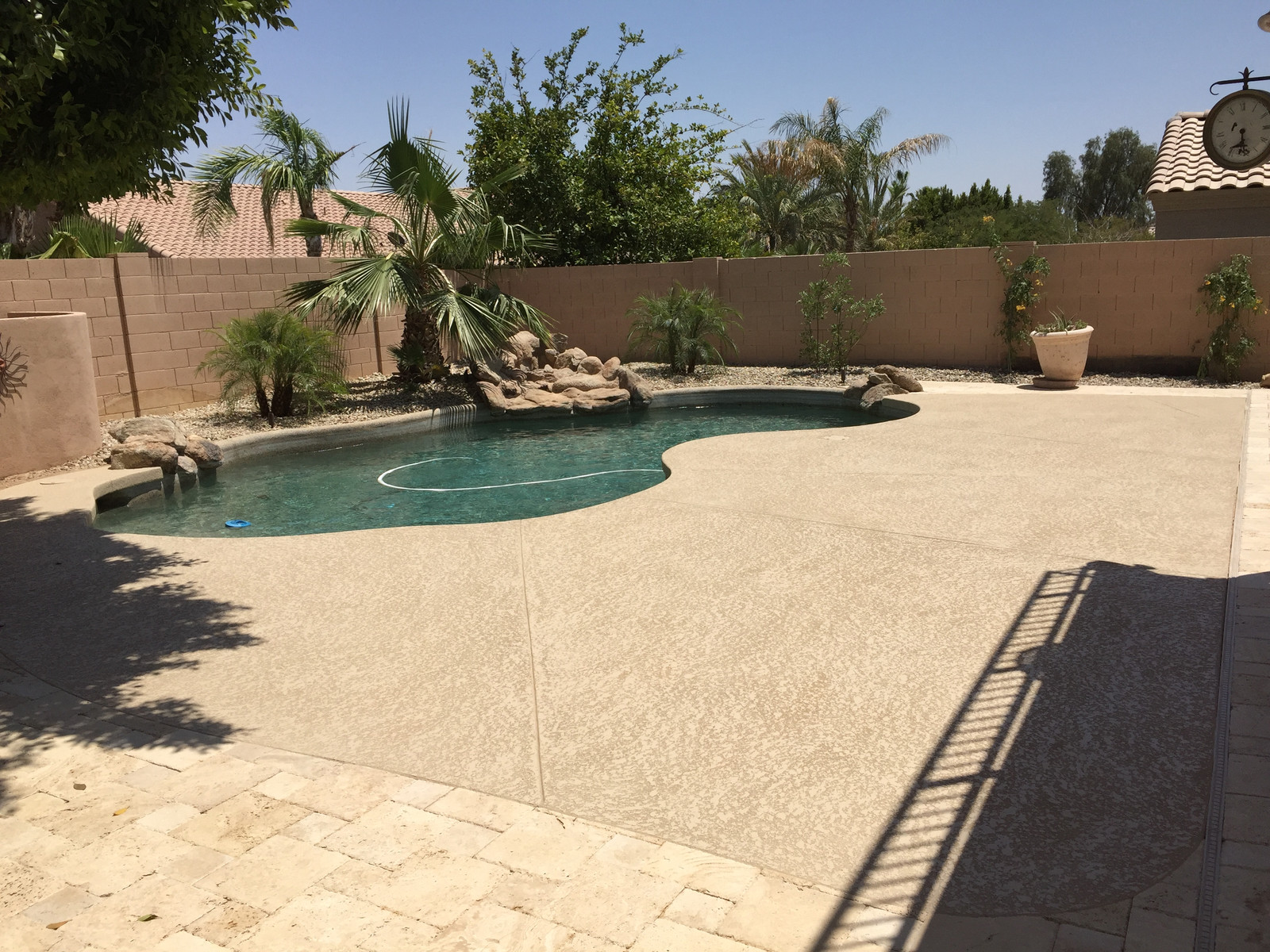 cool deck and travertine with pebble swimming pool | cool deck