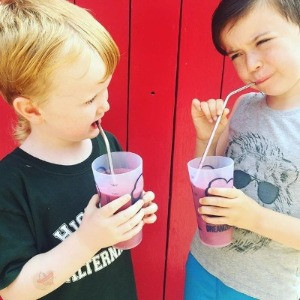 Two Kids using reusable metal straws and reusable cups to drink juice in front of a bright red door.