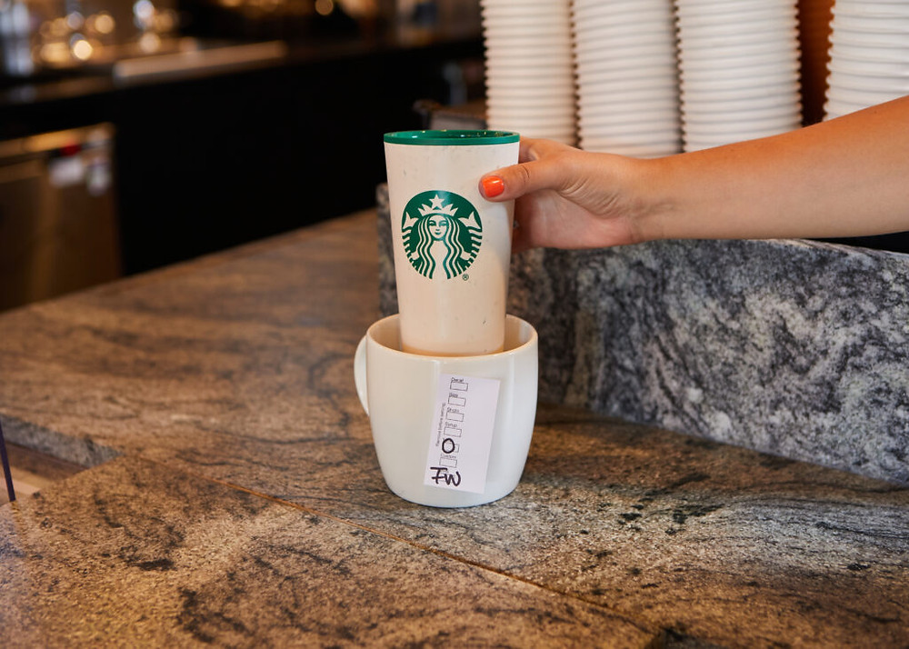 Customer provides their own reusable cup to a Starbucks barista within the store provided vessel for handling reusables.