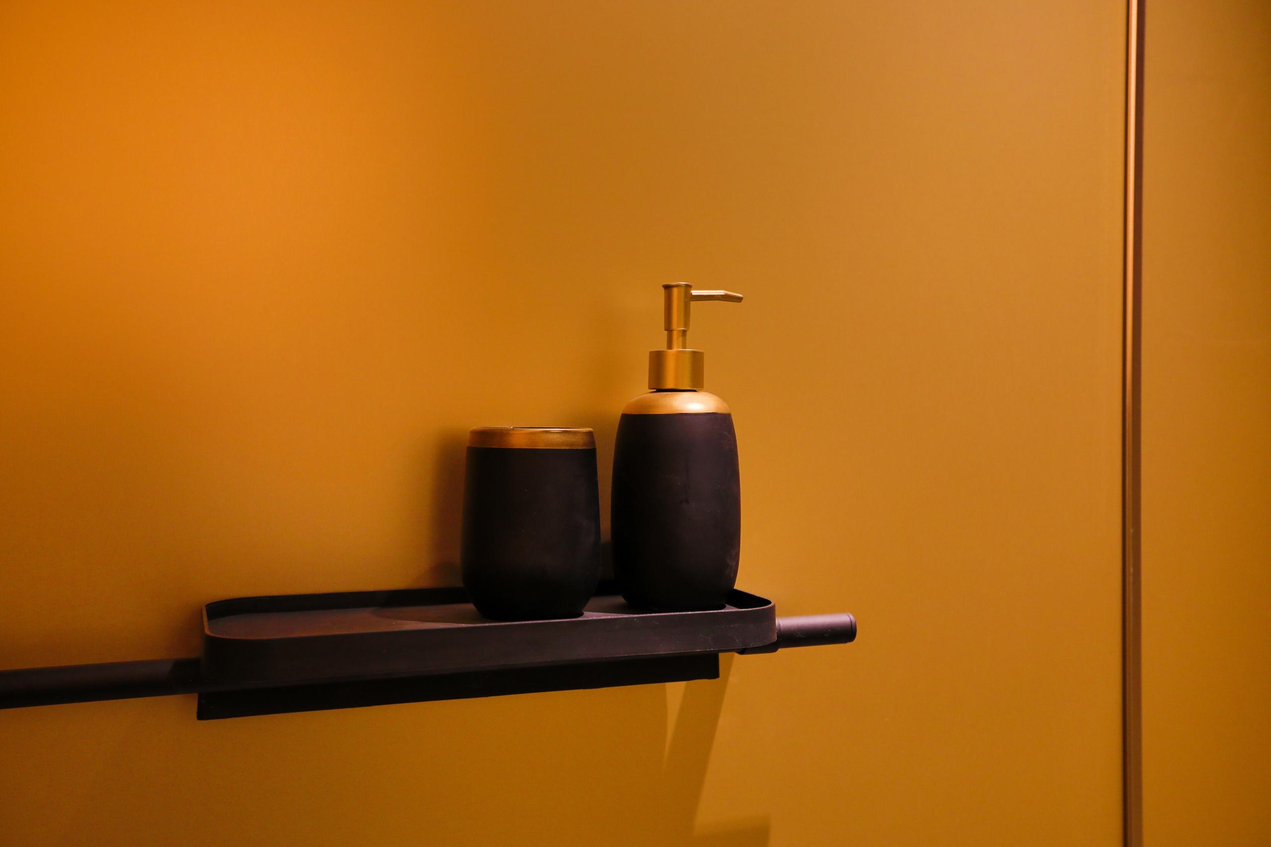 Parois de la salle de bain revêtues de plaques metallisée gold.