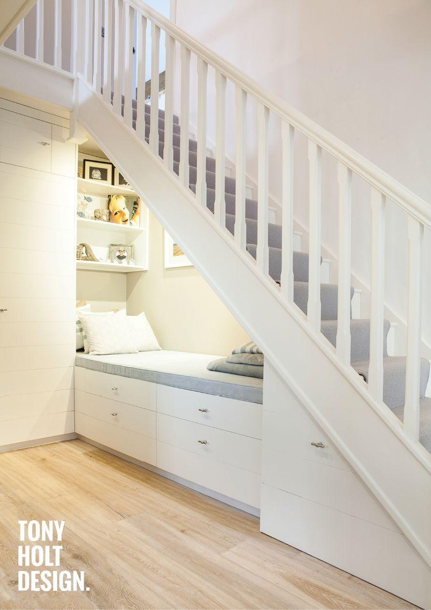 Renfoncement sous l'escalier - Espace mis en valeur par une banquette-lit repos et en dessous tiroirs. Des étagères au dessus de la banquette soulignent cet espace.