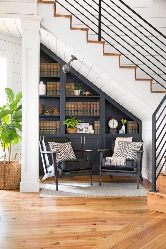 Niches et rangements en partie basse - Travail graphique et ensemble souligné par un décor de peinture gris foncé. Deux fauteuils apportent une note déco à l'ensemble.