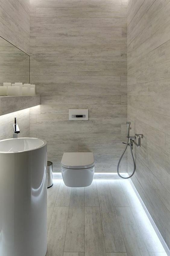 L'éclairage du sol en rappel avec l'éclairage du faux-plafond dans cette salle de bain.