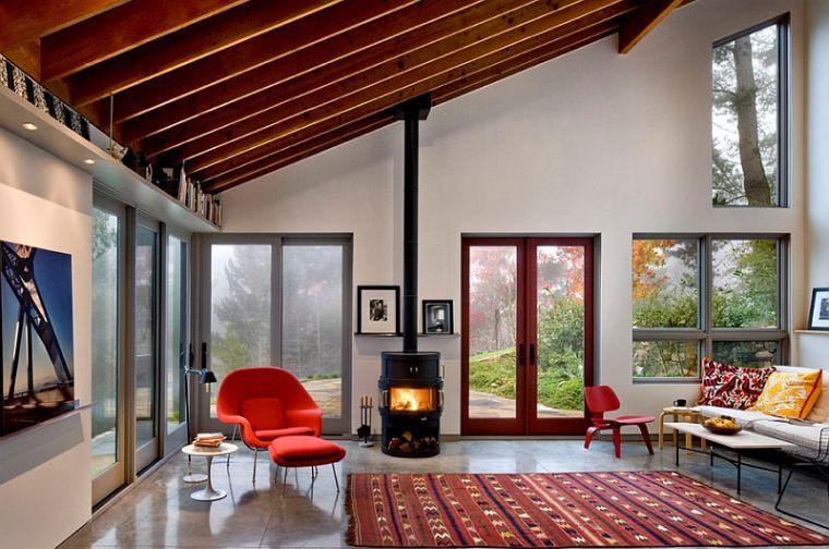 Pour ce salon entouré de baies vitrées qui donnent sur un parc, un poêle à bois réchauffe l'atmosphère. Des éléments de couleur rouge comme le fauteuil et le tapis apportent du dynamisme à cet environnement Feng Shui.