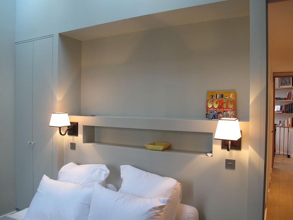 Tête de lit dans un renfoncement avec une niche qui fait office de chevet. Sur les côtés de part et d'autre du lit, appliques au mur.