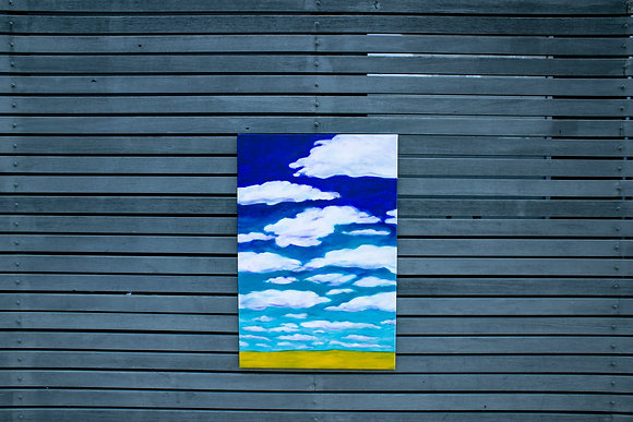 Painting of clouds and landscape hanging on a wall
