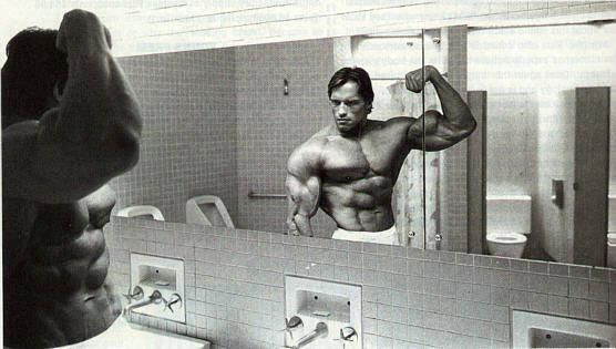 Schwarzenegger flexes in front of the mirror for a reason.