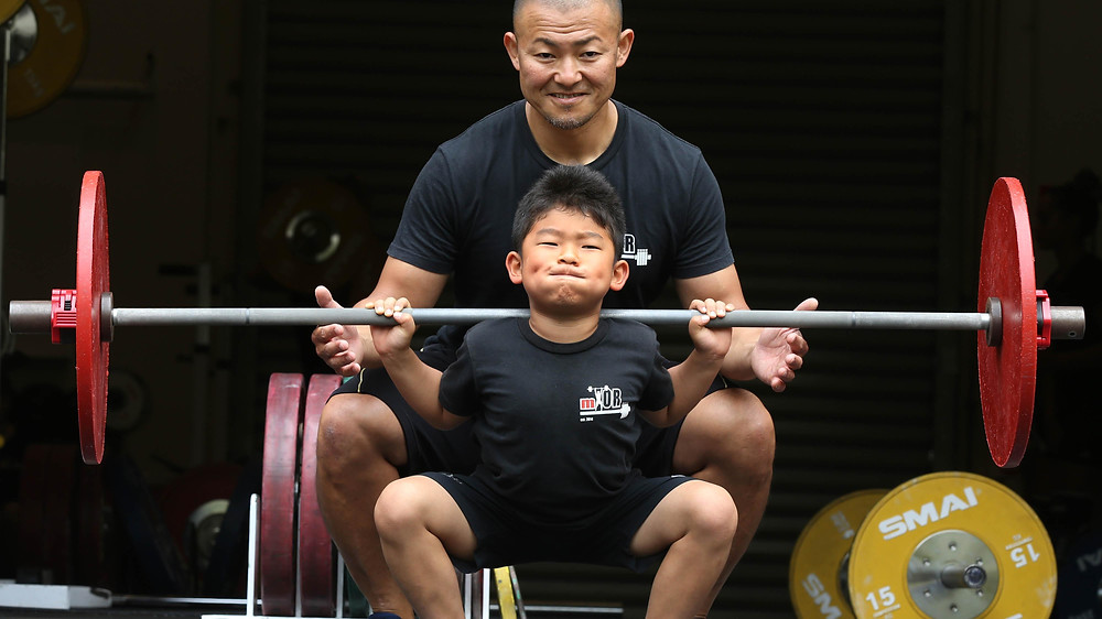 Seven-year-old Go Kotani lifts weights watched by his father Yosuke Kotani. Picture: The West Australian, Nic Ellis, The West Australian
