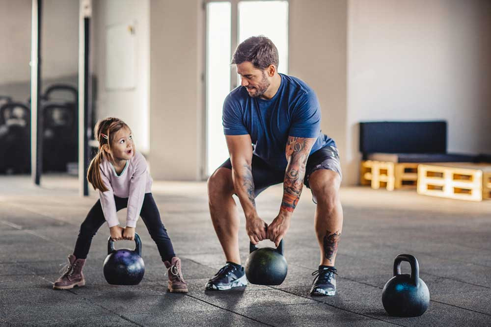 Weightlifting with your child is one way to keep them entertained and healthy.