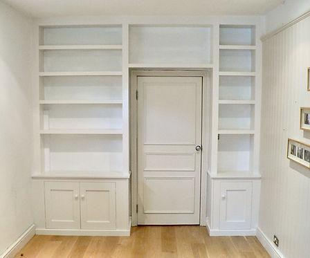 built-in wall to wall chunky shelf unit around doorway with 2 door and 1 door cupboards at base
