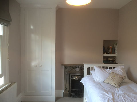 built-in Shaker style two door alcove wardrobe and small shelves in bedroom
