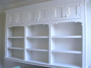 wall mounted painted bookcase with six small cupboards at the top with decorative scrolls