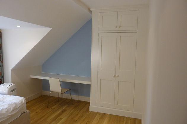 built-in floor to ceiling wardrobe with top doors and desk in attic bedroom
