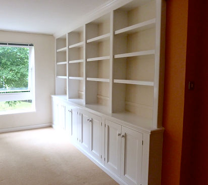 built-in 8 door alcove cupboard with 4 section bookcase above