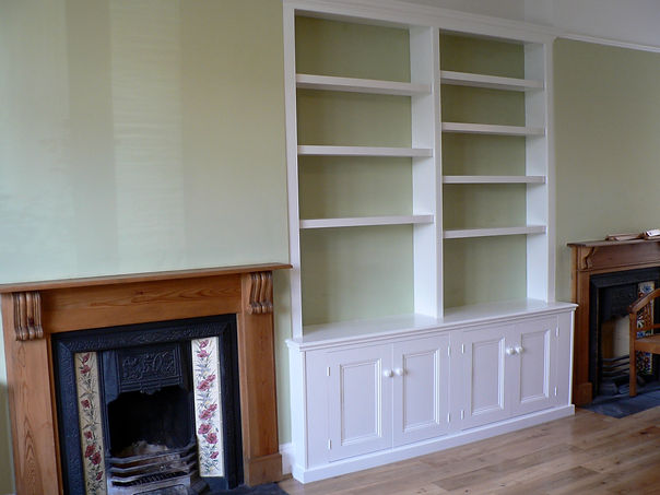 built-in 4 door alcove cupboard with staggered bookcase shelving