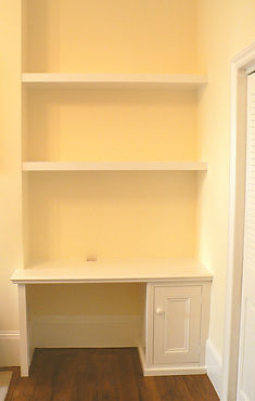built-in floating chunky shelves and desk supported by single door cabinet
