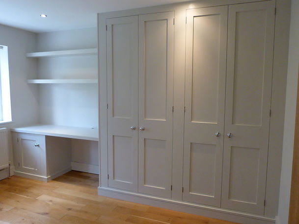 built-in Shaker style four door wardrobe, desk supported by cabinet and floating shelves above