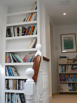 built-in chunky bookcase in hall stairway