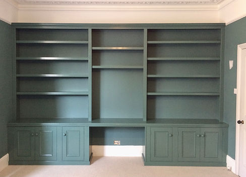 built-in wall to wall shelving unit in three sections with a pair of 3 door alcove cupboards at base