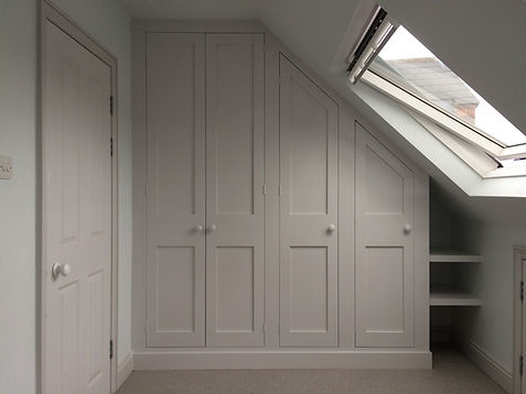 built-in Shaker style under-eaves 4 door wardrobe and small shelves in attic room