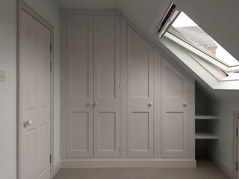 built-in Shaker style under-eaves four door wardrobe in attic room with small alcove shelves