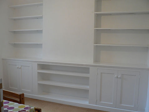 built-in pair of alcove cupboards with floating shelves above and shelving between cupboards