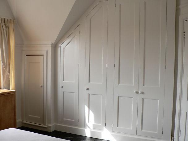 built-in Shaker style under-eaves four door wardrobe plus single cabinet in attic bedroom
