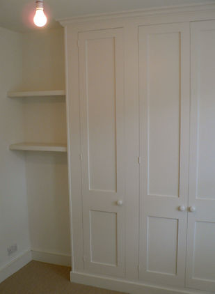 built-in Shaker style three door wardrobe with small shelves