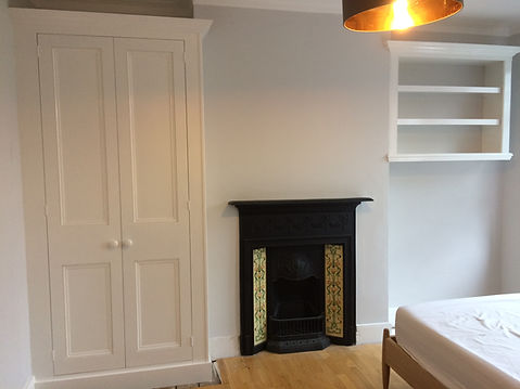 built-in alcove bookcase and wardrobe either side of fireplace