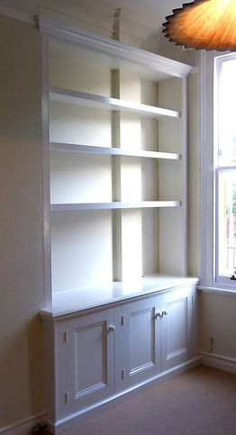 built-in painted three door alcove cupboard and bookcase