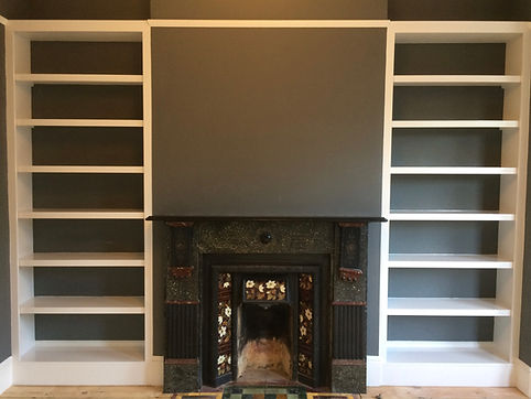 built-in pair of modern alcove bookcases, either side of fireplace
