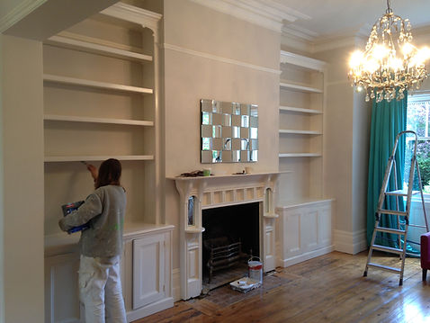 built-in pair of 3 door alcove cupboards and bookcases being painted