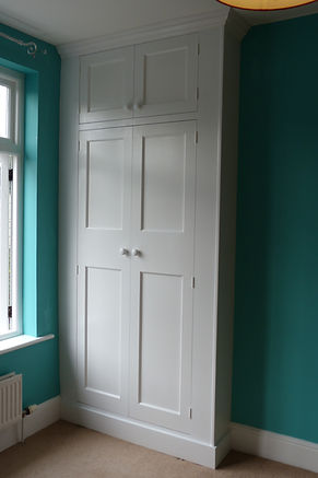 built-in floor to ceiling1930's style wardrobe with two top small doors above two tall doors in alcove