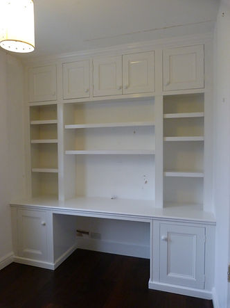 built-in wall to wall desk supported at each end by single door cupboards with bookcase and five door high cupboard above