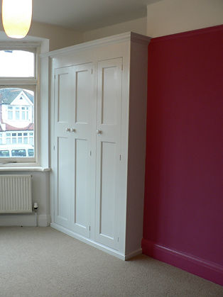 built-in 3 door 1930s style wardrobe with smaller panels at the top
