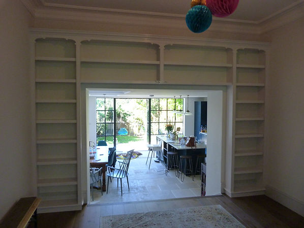 built-in wall to wall bookcase surrounding large opening between library and kitchen