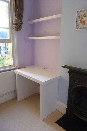 built-in desk and floating shelves in bedroom alcove