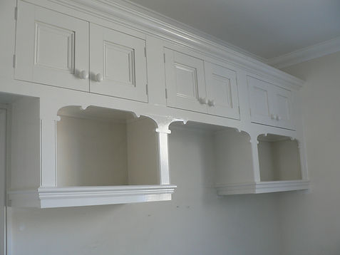 built-in high cupboards with bespoke decorative shelving