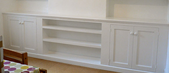 built-in Shaker style wall to wall unit, pair of alcove cupboards joined by low shelving