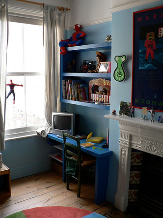 built-in desk and floating shelves in alcove in child's bedroom