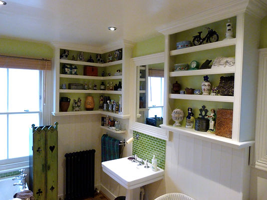 built-in L-shaped shelving unit and decorative shelving in bathroom
