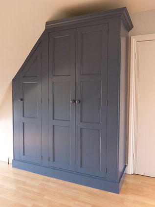 built-in 1940's style 3 door under-eaves wardrobe in sloping roof attic room